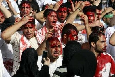 Shi'ite Muslim women take photographs of bleeding men after they were cut on their heads with blades during a ceremony marking Ashura in Nabatieh, south Lebanon, December 27, 2009.