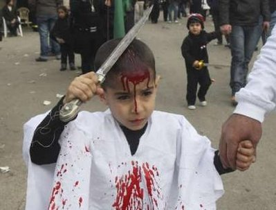 A Shi'ite Muslim boy taps his head with a blade to draw blood during a ceremony marking Ashura in Nabatieh, south Lebanon, December 27, 2009