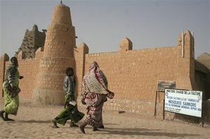 AP Photo - People dressed in colorful dress walk near the Sankore Mosque, a United Nations world heritage cultural site, which would not be allowed under the rule of Islamic militants who ruled the city until French troops took control, in Timbuktu, Mali, Thursday Jan. 31, 2013. Many things have changed in Timbuktu since French troops parachuted in several days ago to take control of the area from Islamic militants, and now there is a growing sense of freedom.