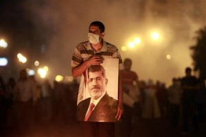 File photo of an injured supporter of deposed Egyptian President Mohamed Mursi carrying a poster of Mursi as they run from tear gas fired by riot police during clashes on the Sixth of October Bridge over the Ramsis square area in central Cairo