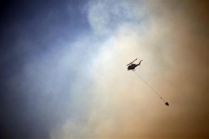 A helicopter drops water on a fire approaching homes near the Blue Mountains suburb of Blackheath