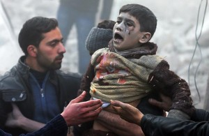 Men help a wounded boy who survived what activists say was an airstrike by forces loyal to Syrian President Bashar al-Assad in the Duma neighbourhood of Damascus