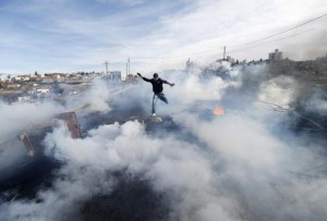 A Palestinian protester jumps as tear gas fired by Israeli soldiers rises during clashes in Jalazoun refugee camp near Ramallah