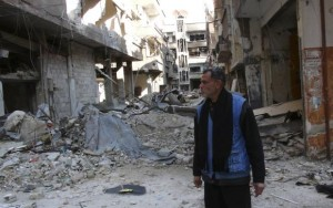 A man stands amid the rubble of damaged buildings at the Palestinian refugee camp of Yarmouk, south of Damascus