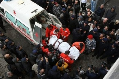 Red Cross paramedics carry to the body of one of the victims of the Ethiopian Boeing 737 crash into the mortuary of a government hospital in Beirut